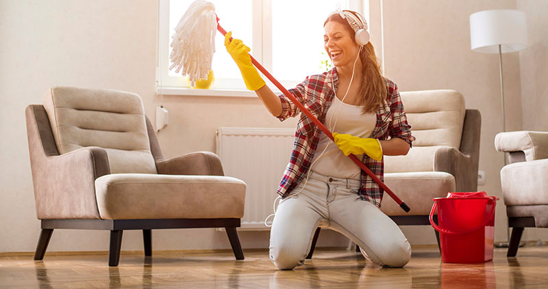 Young Woman with Headphones and Mop Ready For Living Room Cleaning