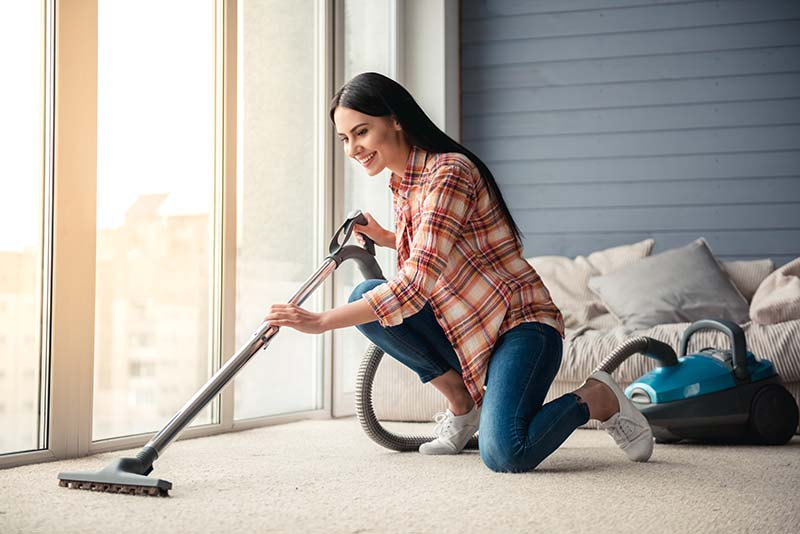Beautiful Young Woman Vacuuming Floor at Home